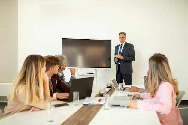 オフィスで新しいプロジェクトに取り組んでいる間多民族のビジネス人々のグループに戦略を説明する成熟した実業家