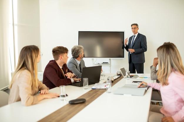 Зрелый бизнесмен объясняет стратегию группе многоэтнических деловых людей во время работы над новым проектом в офисе
