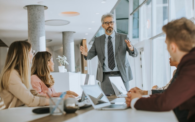 Зрелый бизнесмен, объясняя стратегию группе многонациональных деловых людей во время работы над новым проектом