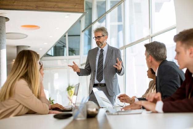 新しいプロジェクトに取り組んでいる間多民族のビジネス人々のグループに戦略を説明する成熟した実業家