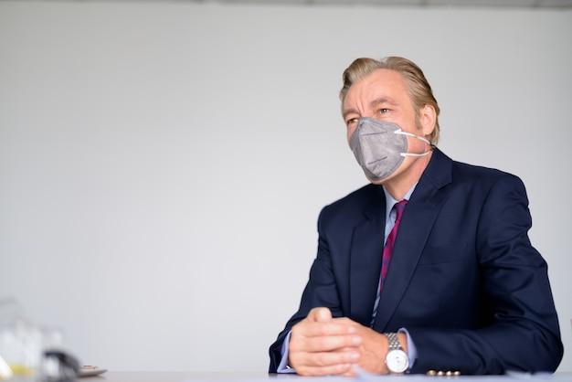 仕事でコロナウイルスの発生からの保護のためのマスクを着用しながら会議を行っている成熟した実業家