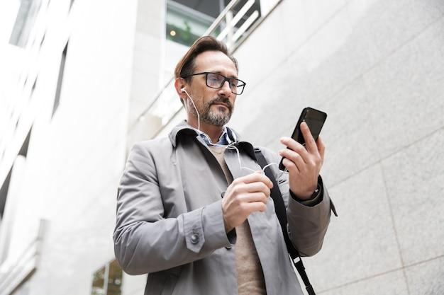 Зрелый бизнесмен в очках, используя мобильный телефон и наушники, стоя возле офисного здания
