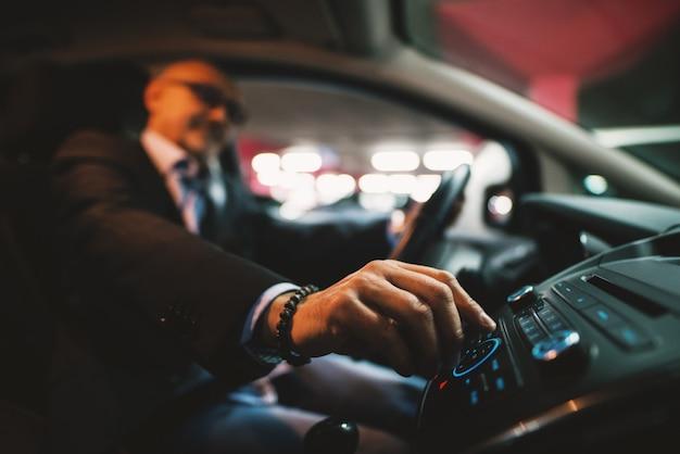 소송에서 성숙한 사업가 차를 운전하는 동안 그의 스테레오에 볼륨을 조정합니다.