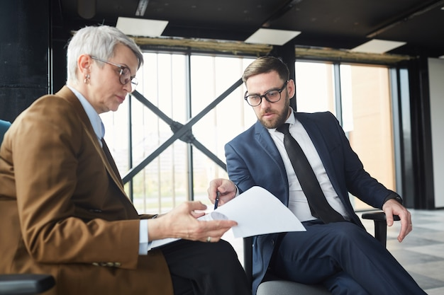 Зрелый бизнесмен в костюме, указывая на документ и обсуждая его с бизнес-леди, сидя в новом пустом офисном здании