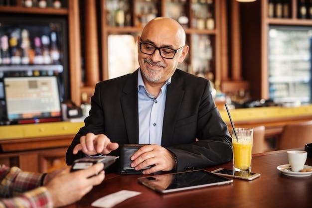 成熟した実業家は、コーヒーショップで彼のクレジットカードで法案を払っています。