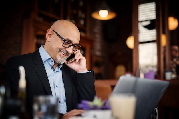 成熟した実業家は、ラップトップを使用してコーヒーショップのテーブルに座っている間、彼の通話中に笑みを浮かべてください。