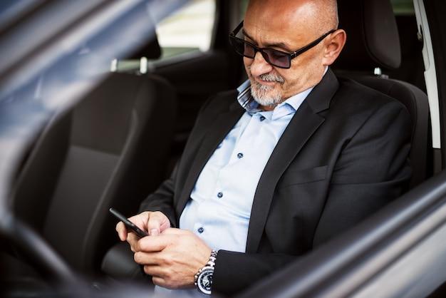 成熟したビジネスマンは車を運転している間彼の電話を使用しています。