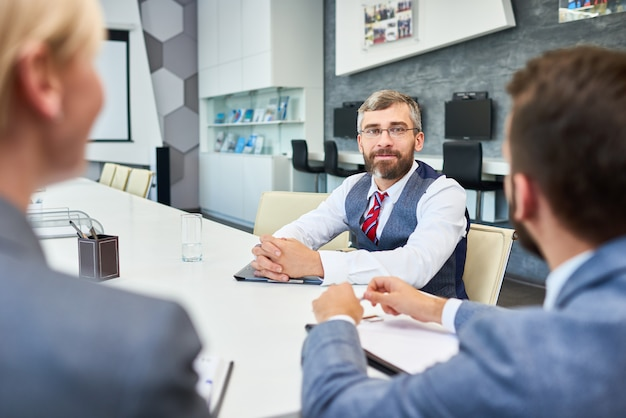Mature businessman listening to partners in meeting