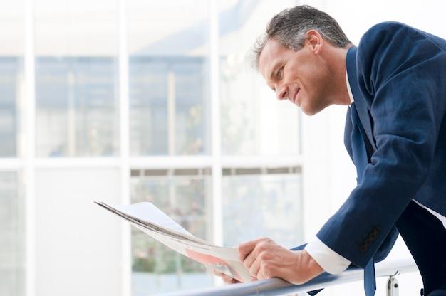 成熟したビジネスマンを探して、近代的なオフィスで新聞を読む