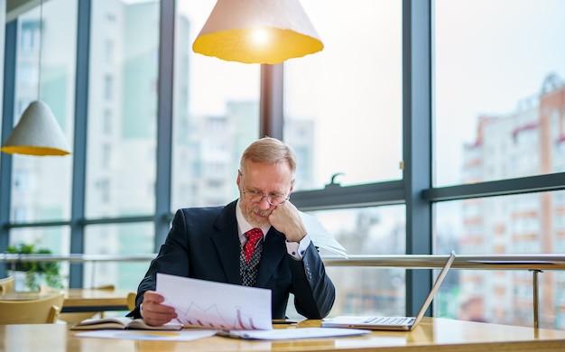 彼のオフィスでドキュメントを見ている成熟したビジネスマン
