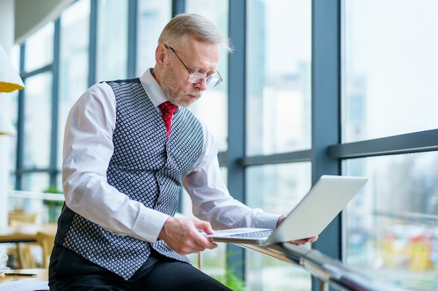 印刷された文書を読んでラップトップを見ている成熟したビジネスマン。
