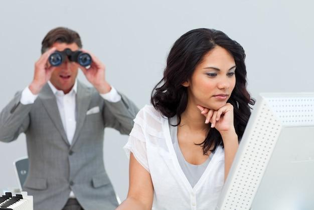 熟練したビジネスマン、双眼鏡で同僚のコンピュータを見て