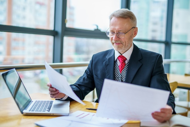 Mature businessman looking at laptop reading and printing improvements sitting near the window in his office. panoramic city view background. business photo.
