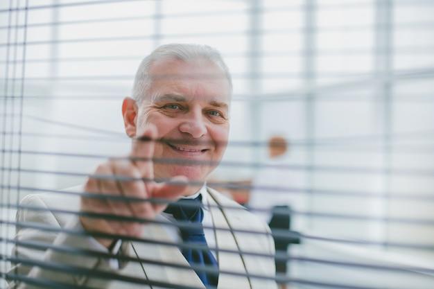 Mature businessman looking through office window blinds