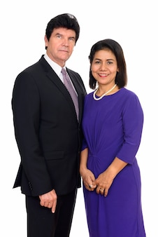 Mature businessman and mature asian businesswoman together isolated against white wall