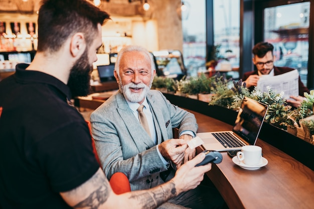 Mature businessman paying with contactless credit card with nfc technology.