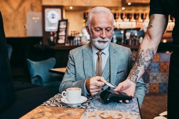Зрелый бизнесмен, оплата бесконтактной кредитной картой с технологией nfc.
