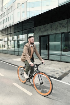Зрелый бизнесмен, едущий на велосипеде на работу по улице в городе