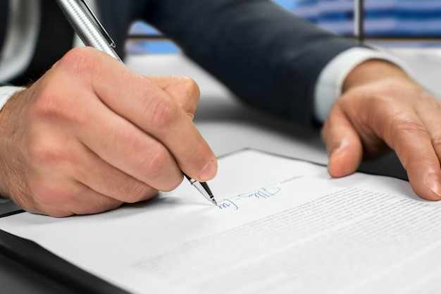 Mature businessman's hand signing document. man signs paper beside window. new insurance policy. official letter to a partner.