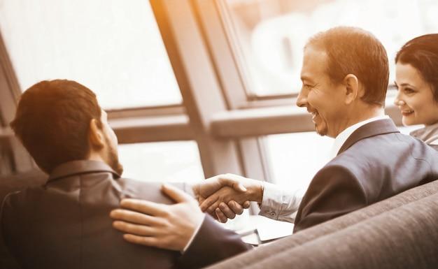 彼のパートナーとの契約を結ぶために握手する成熟したビジネスマン