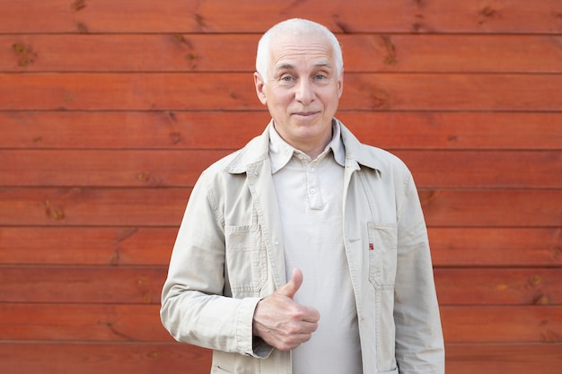 Mature businessman showing thumb up on wooden wall background