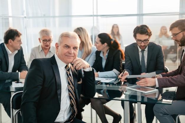 オフィスの机に座っている成熟したビジネスマン