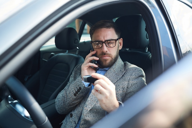 Mature businessman sitting in car salon and talking on mobile phone