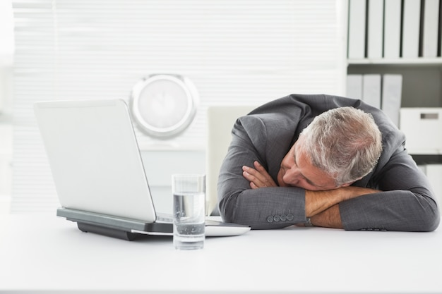 Mature businessman sleeping on desk