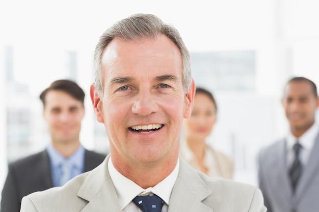 彼の後ろにチームとカメラで笑顔熟練したビジネスマン