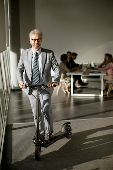 Mature businessman standing by the office window with electric scooter