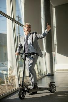 電動スクーターでオフィスの窓のそばに立っている成熟した実業家