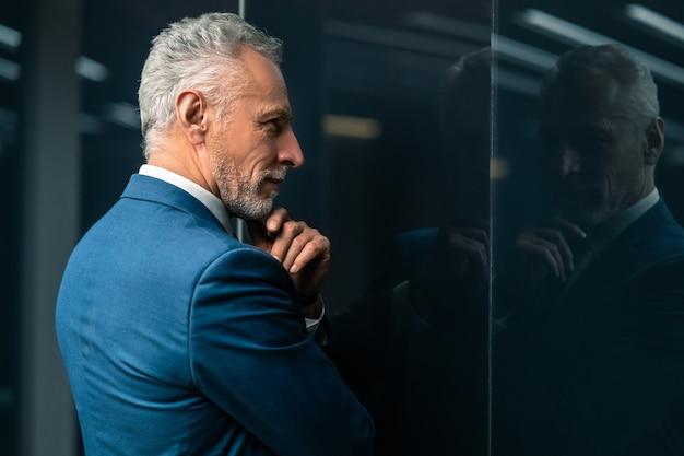 The mature businessman standing indoor