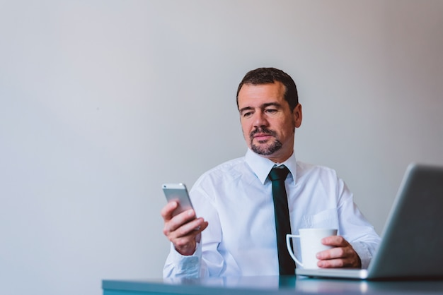 Mature businessman in suit using cell phone at desk in small office.
