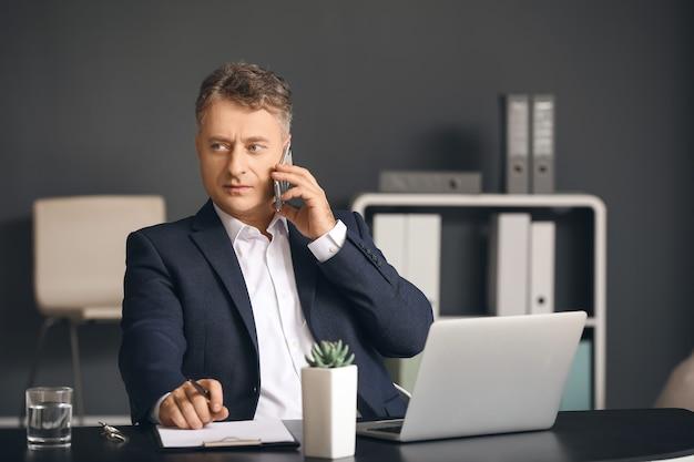 オフィスで携帯電話で話している成熟したビジネスマン