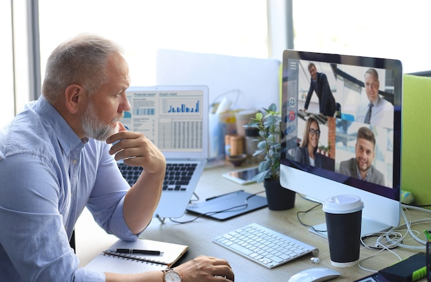 Mature businessman talking to his colleagues in video conference. multiethnic business team working from office using computer pc, discussing financial report of their company