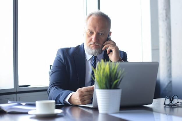Зрелый бизнесмен разговаривает по смартфону и с помощью компьютера во время работы в офисе.