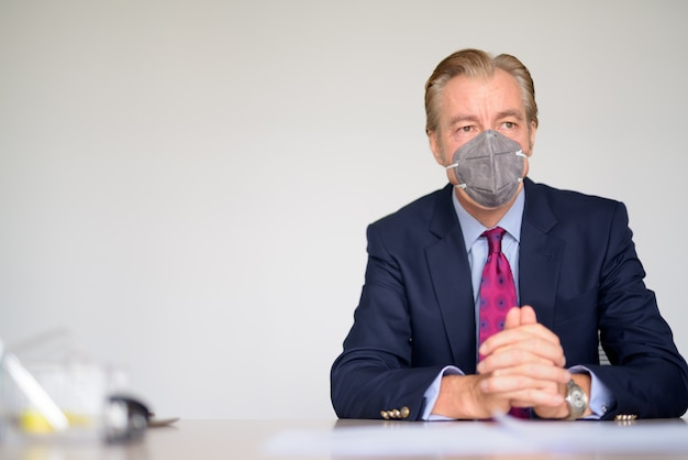 仕事でコロナウイルスの発生からの保護のためのマスクと考えて成熟した実業家