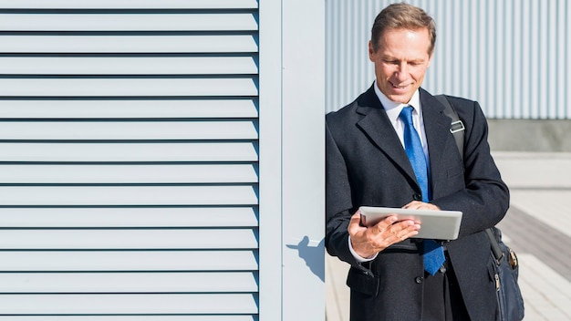 Зрелый бизнесмен используя цифровую таблетку на outdoors