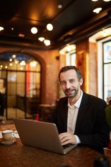 Зрелый бизнесмен, используя ноутбук в ресторане