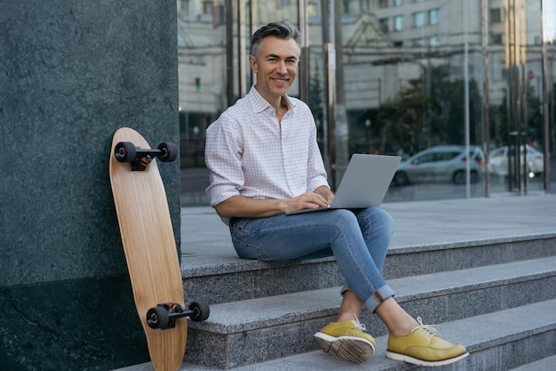 야외에서 노트북을 사용 하여 성숙한 사업가입니다. 성공적인 프리랜서, 카메라를보고 웃고