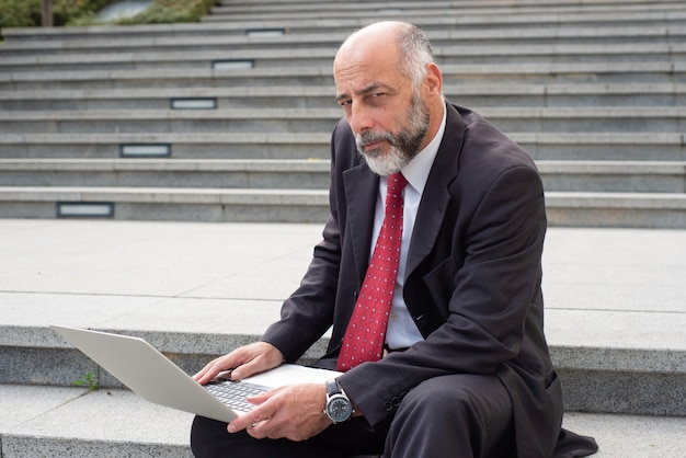 Mature businessman with laptop computer on street