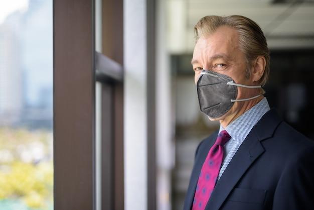 職場の窓辺でコロナウイルスの発生から保護するためのマスクを持つ成熟した実業家