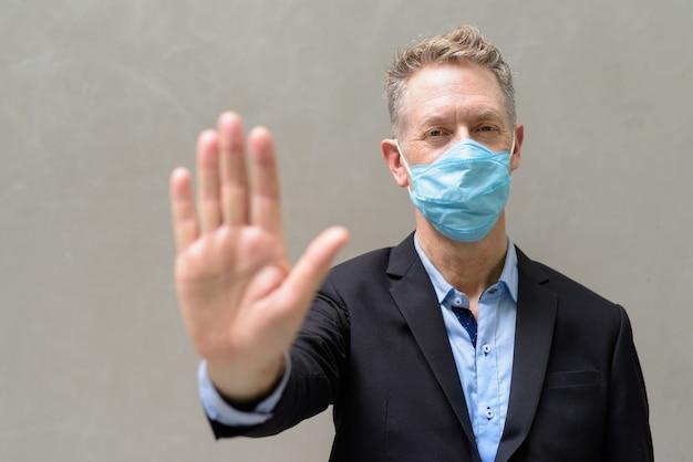 屋外停止ジェスチャーを示すマスクを持つ成熟した実業家