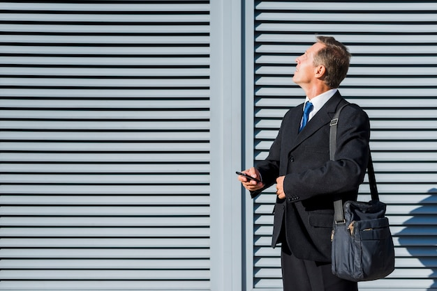 Mature businessman with mobile phone looking up