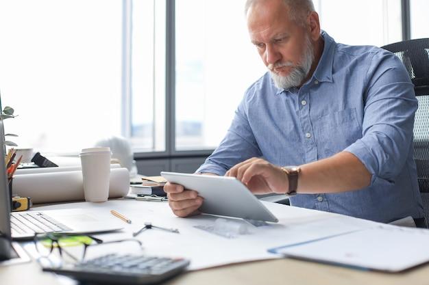 Зрелый бизнесмен, работающий с помощью цифрового планшета, сидя в современном офисе.