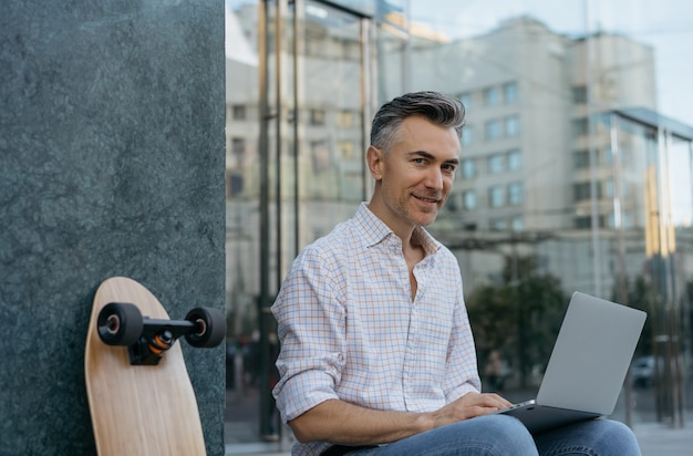 성숙한 사업가 작업, 노트북을 사용하여 카메라를보고 웃고