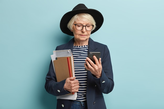 Imprenditrice matura concentrata nel telefono cellulare, attende una chiamata importante dal partner