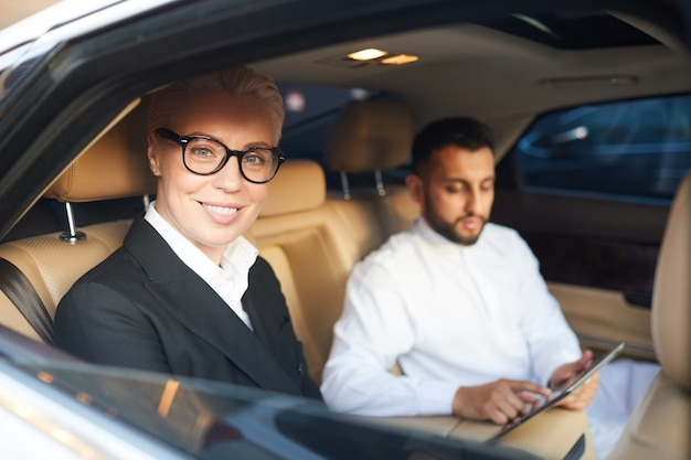 Mature businesswoman in eyeglasses smiling at camera while sitting in the car with his colleague in the background