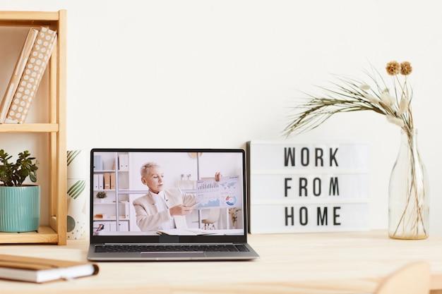 Зрелая бизнес-леди держит финансовую графику и проводит бизнес-презентацию онлайн с монитора ноутбука