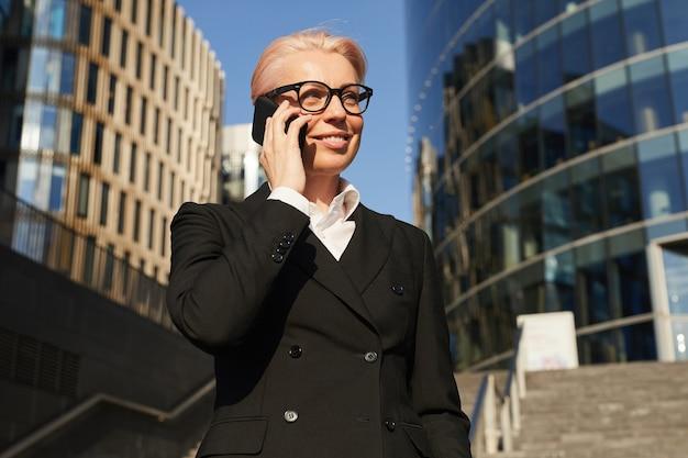 백그라운드에서 사무실 건물과 도시에 서있는 동안 휴대 전화에 얘기하는 검은 양복에 성숙한 사업가